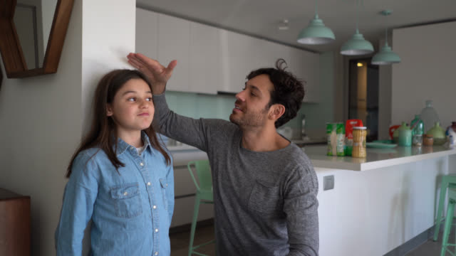 loving father measuring daughter with excitement against the wall both celebrating her growth - in cima video stock e b–roll