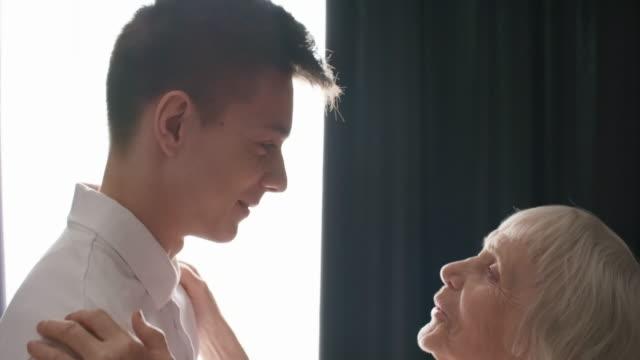 loving grandmother hugging and kissing grandson - внук стоковые видео и кадры b-roll