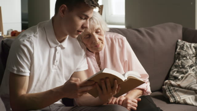 Loving Grandson Reading Book to Grandmother Medium shot of young man sitting on sofa in living room and reading book aloud to grandmother leaning on his shoulder grandmother stock videos & royalty-free footage