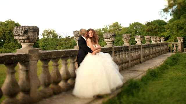 loving groom holding his beautiful bride on green lawn near old stone balustrade and kisses her in neck - balaustrata video stock e b–roll