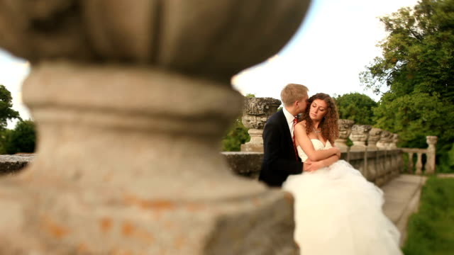 loving groom holding his beautiful bride on green lawn near old stone balustrade and kisses her hair - balaustrata video stock e b–roll