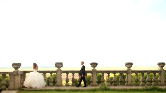 loving groom walks towards beautiful bride on green lawn near old stone balustrade and embaces her with kiss - balaustrata video stock e b–roll