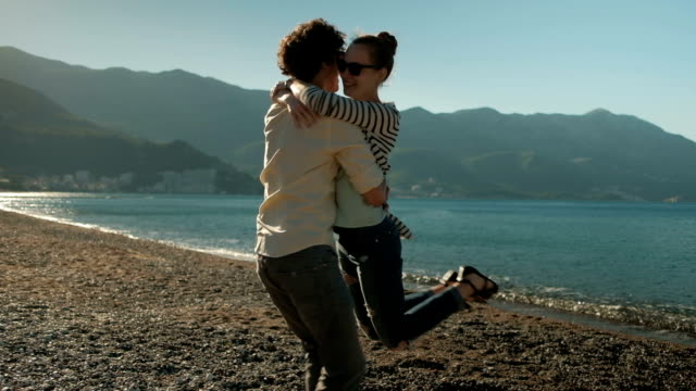 Loving happy couple walk on lake, woman running hugs outdoors video