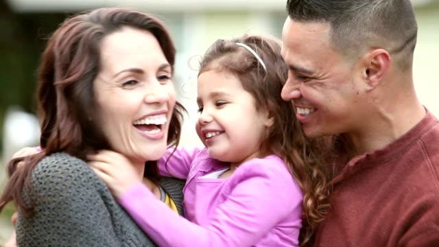 Loving Hispanic family with little girl, hugs and kisses
