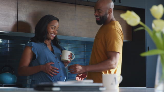liebenhispanische mann mit schwangeren frau zu hause in der küche zusammen - schwanger stock-videos und b-roll-filmmaterial