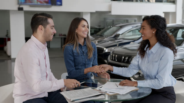 Loving Latin American couple closing a deal on a car signing a contract at the dealership with friendly black saleswoman Loving Latin American couple closing a deal on a car signing a contract at the dealership with friendly black saleswoman - Consumerism concepts car salesperson stock videos & royalty-free footage