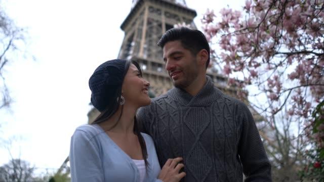 Loving latin american couple walking near the Eiffel Tower while talking
