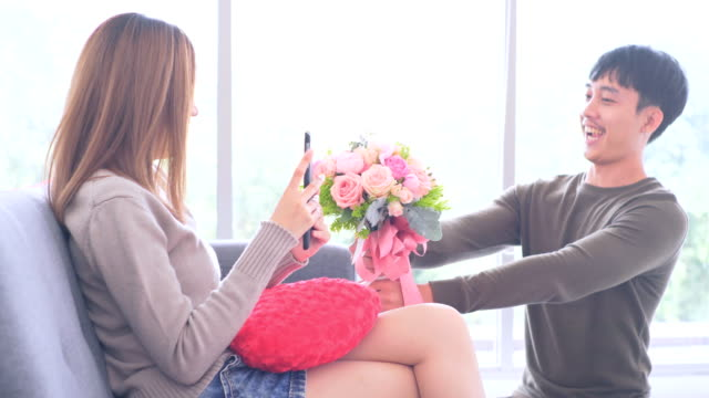 loving man giving a bunch of flowers to a smiling beautiful woman at Home