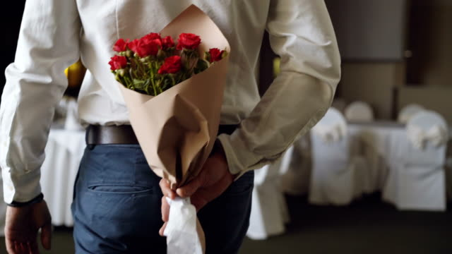 Loving man is hiding red roses behind his back bringing beautiful bouquet for his date in restaurant. Flowers, romantic relationship and dating concept.