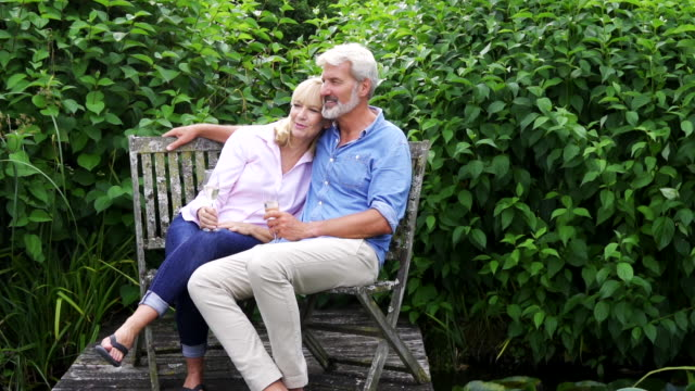 Loving Mature Couple Celebrating With Champagne Sitting On Chairs On Wooden Jetty By Lake