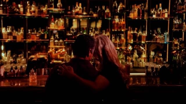 Loving mature couple flirting and sitting on bar counter Elegant senior couple sitting on bar counter and enjoying romantic date at luxurious retro bar bar counter stock videos & royalty-free footage