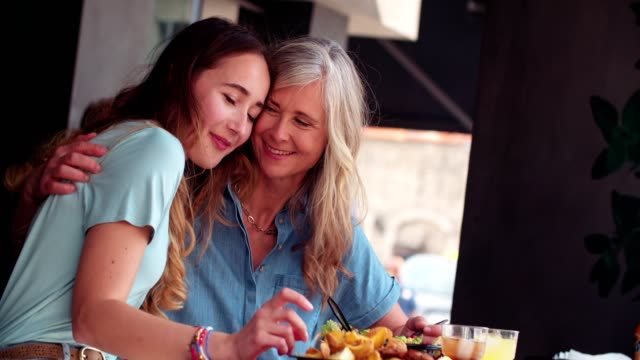 loving mature mother and daughter sharing a meal and hugging - genitori video stock e b–roll