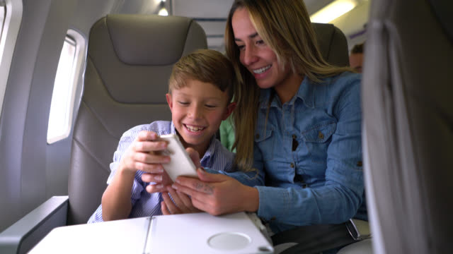 사랑 엄마와 아들이 공기 중에 스마트폰 연주 비행 둘 다 웃 고 - airplane seat 스톡 비디오 및 b-롤 화면