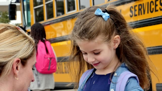 loving mom gives her give her young daughter advice before the girl boards school bus - school buses stock videos and b-roll footage
