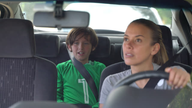 Loving mom looking at her son through the rear view mirror while he tells her about the soccer practice