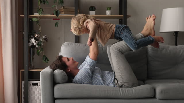 Loving mom lying on couch play with preschool son