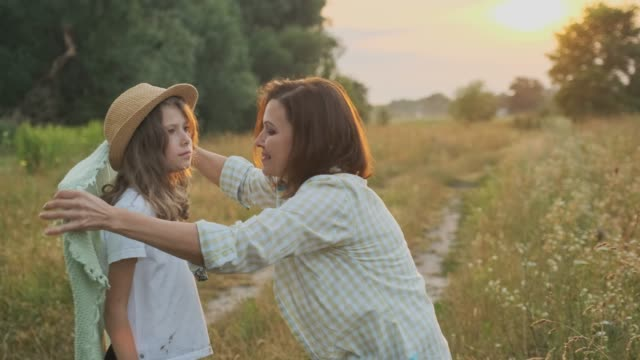 Loving moms puts on daughter knitted blanket, hugging child, summer nature background, golden hour Loving moms puts on daughter knitted blanket, hugging child, summer nature background, golden hour styles stock videos & royalty-free footage