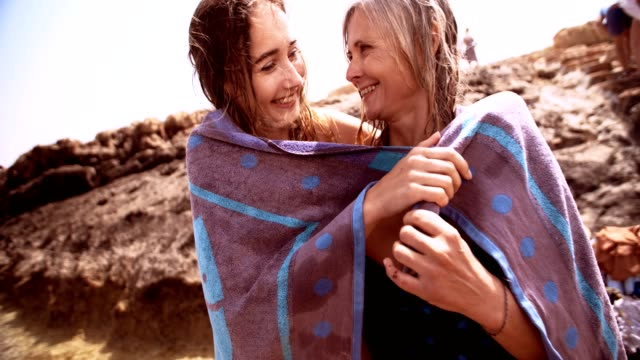 loving mother and daughter covered with beach towel after swim - wnuczę filmów i materiałów b-roll