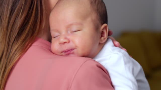 Loving Mother Cuddling Sleeping Newborn Baby Son Over Shoulder Loving Mother Cuddling Sleeping Newborn Baby Son Over Shoulder yawning stock videos & royalty-free footage