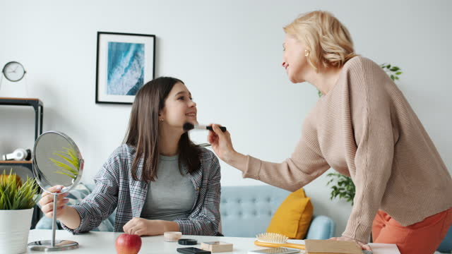 Loving mother helping teenage daughter with make-up applying cosmetics enjoying leisure time at home video