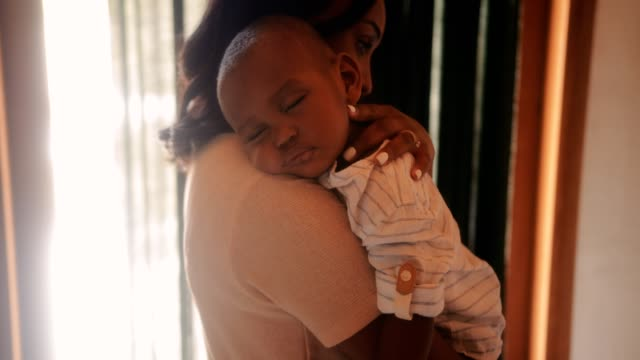 Loving mother holding sleeping baby boy in her arms