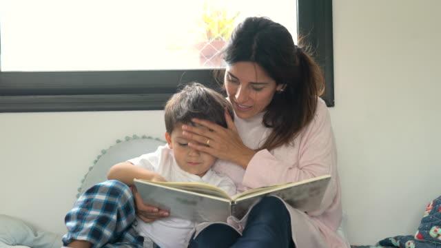 kärleksfull mamma kysser hennes sons huvud medan du läser en godnattsaga hemma - enbarnsfamilj bildbanksvideor och videomaterial från bakom kulisserna