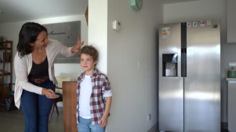 vidéos et rushes de mère aimante mesurant le fils contre le mur célébrant sa croissance - en haut