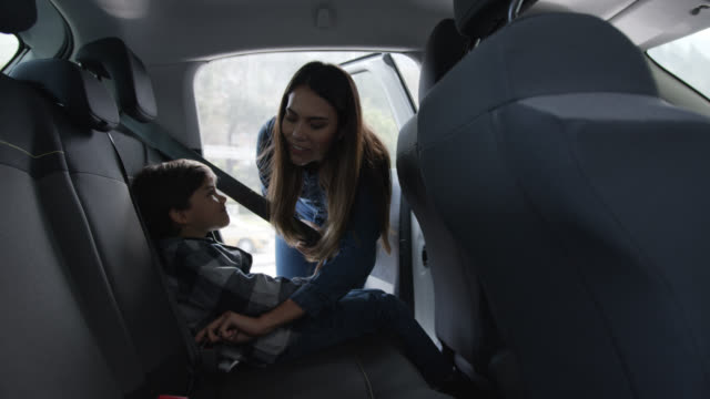 vídeos de stock, filmes e b-roll de mãe amorosa protegendo seu filho no banco de trás com cinto de segurança - veículo terrestre