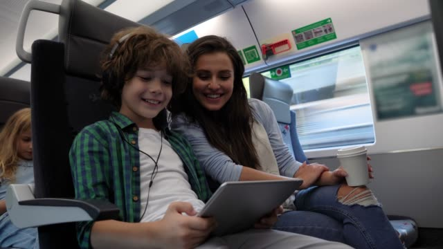 Loving mother watching her son play with digital tablet having fun while commuting on train