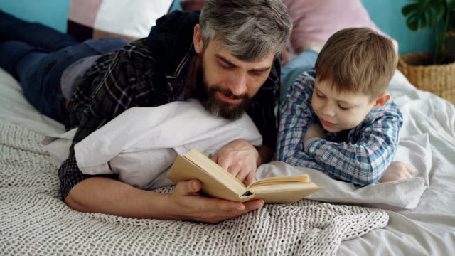 Loving parent bearded man is reading interesting book to his curious little son on double bed at home. Parenthood, happy people, love and family concept. video