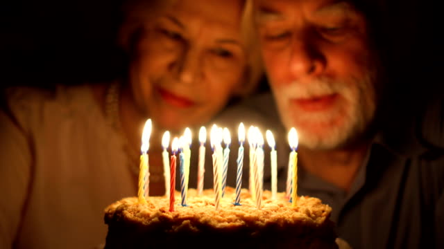 Loving senior couple celebrating anniversary with cake at home in the evening. Blowing out candles Loving senior couple celebrating anniversary with cake at home in the evening. Happy elderly family hugging, cuddling together, make wishes and blowing out candles. Focus on the cake candle stock videos & royalty-free footage