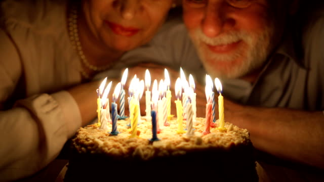 Loving senior couple celebrating anniversary with cake at home in the evening. Blowing out candles video