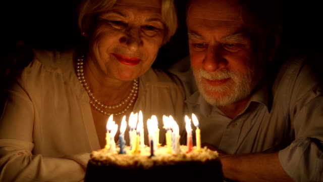 loving senior couple celebrating anniversary with cake at home in the evening. blowing out candles - годовщина стоковые видео и кадры b-roll