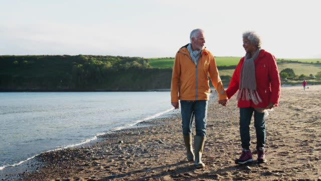 liebevolles senior-paar hält hände am ufer im winterstrandurlaub entlang - in zeitlupe gedreht - seniorenpaar stock-videos und b-roll-filmmaterial