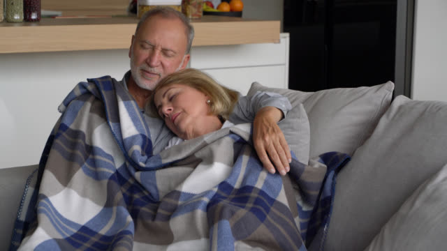 Loving  senior couple sleeping on couch with a cover on top looking very comfortable
