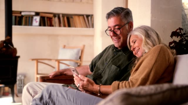 loving senior couple using smartphone and laughing together at home - coppia anziana video stock e b–roll