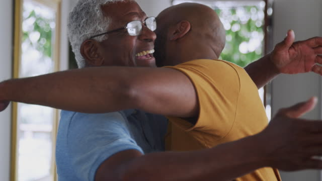 Loving Senior Father Hugging Adult Son Indoors At Home Loving senior African American father hugging and greeting adult son indoors at home - shot in slow motion father stock videos & royalty-free footage