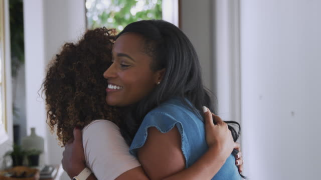 Loving Senior Mother Hugging Adult Daughter Indoors At Home