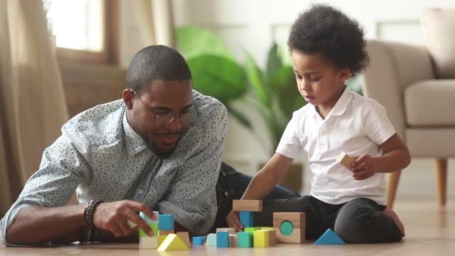loving single black father helping little kid son playing together - klocek filmów i materiałów b-roll