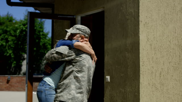 Loving wife meeting soldier at home Cheerful woman running out of house and embracing military husband back at home excited with happiness homecoming stock videos & royalty-free footage