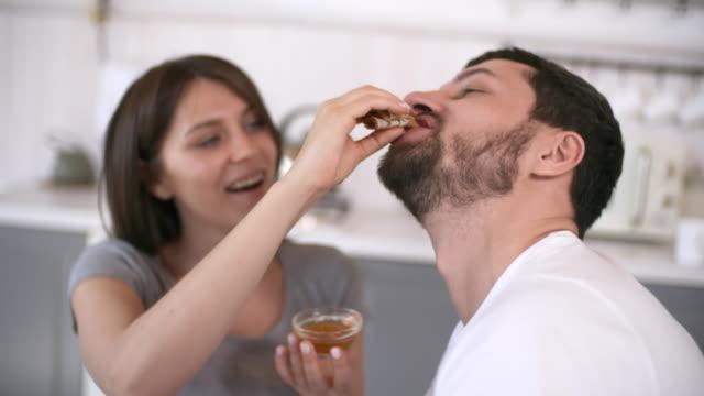 loving woman feeding pancake to man - pancake video stock e b–roll