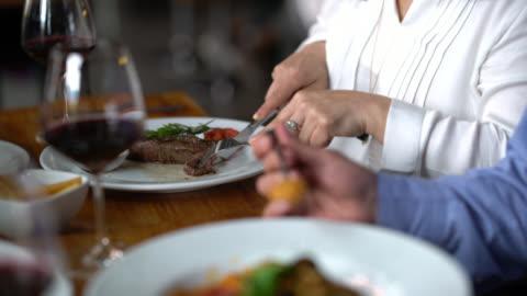 vídeos y material grabado en eventos de stock de amante mujer compartir su carne con pareja en un restaurante mirando muy feliz - cortar