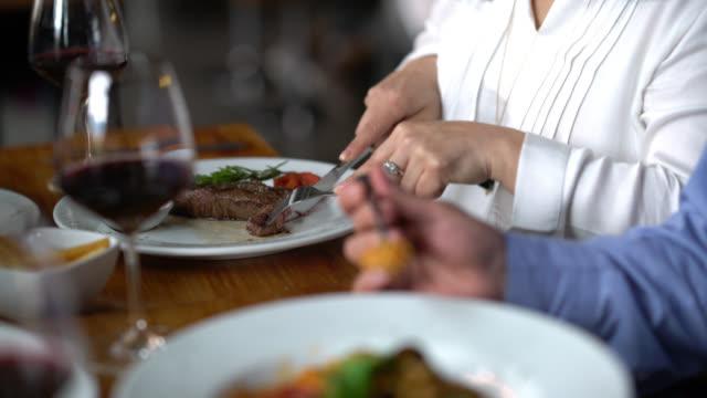 vidéos et rushes de femme aimante partager sa viande avec partenaire dans un restaurant à l'air très heureux - fourchette