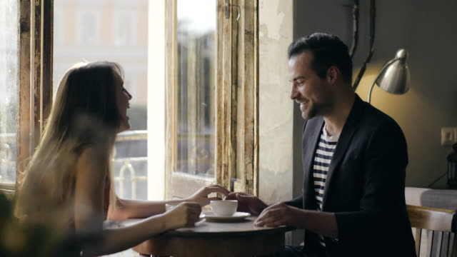 Loving young couple holding hands at table a lonely cafe. Romantic date in cafe video