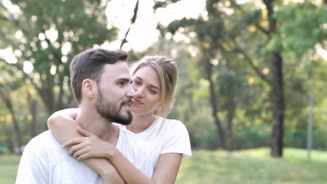 화창한 날 공원에서 젊은 부부 사랑. 자연에 발렌타인의 하루입니다. 커플 사랑 개념에. 슬로우 모션 - 이성 커플 스톡 비디오 및 b-롤 화면