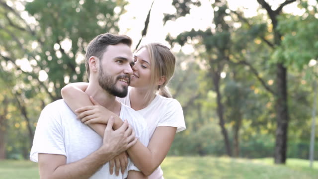 loving young couple kissing in a park on a sunny day. valentine's day in nature. couple in love concept. slow motion - couple portrait caucasian video stock e b–roll