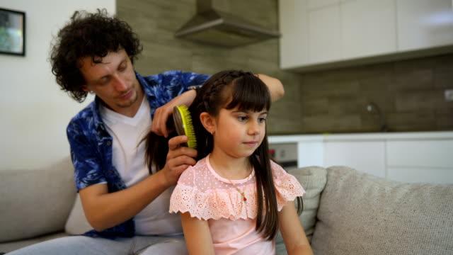 amare il giovane padre che si spazzola i capelli della graziosa figlia bambina giocando a legare seduto a casa, curando la babysitter padre single che aiuta la bambina a preparare l'acconciatura preparandosi al mattino - padre single video stock e b–roll