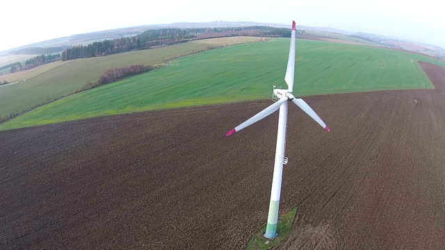 Low aerial view of wind turbine power plants video