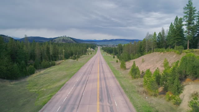 Low altitude flight along the Highway MT 200 near Greenough, Montana, in early spring. Stormy weather, with the dramatic cloudy sky and heavy snowstorm at the horizon. Drone video with the forward and ascending camera motion. - vídeo