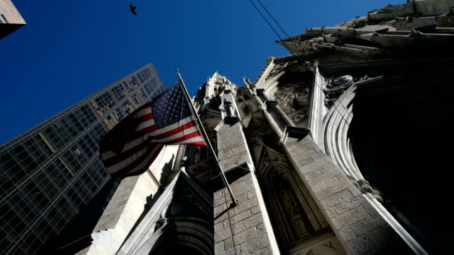 Low angle american flag fluttering at Saint Patrick Church in New York video
